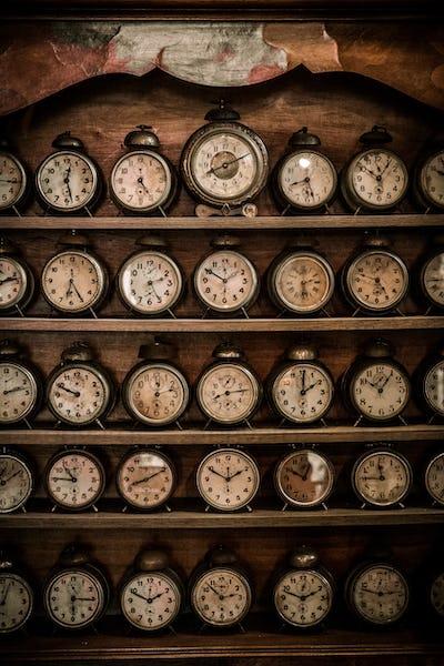Vintage alarm clocks on a wooden shelf