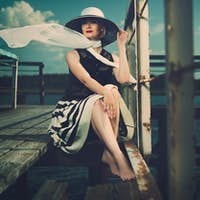 Beautiful woman wearing hat and white scarf sitting on old wooden pier