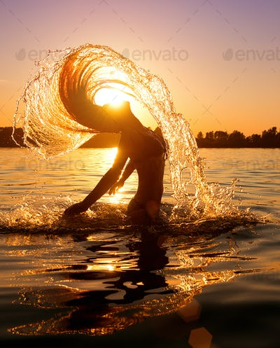 Beauty model girl splashing water with her hair