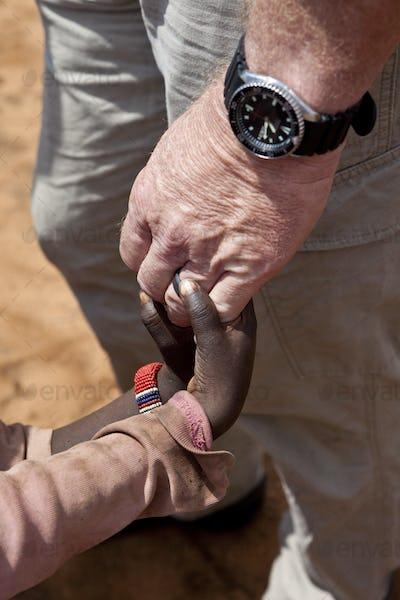 aid worker's hands holding children's hands