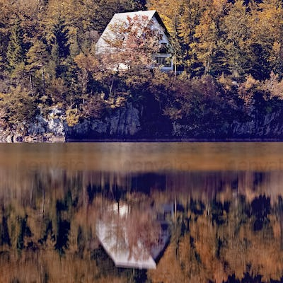 House on rock with reflection in lake early in the morning