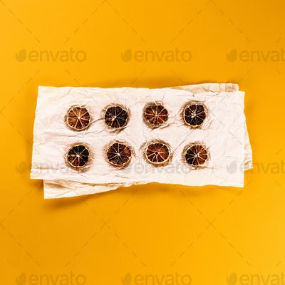 Souvenir dried lemons on a crumpled paper and yellow background