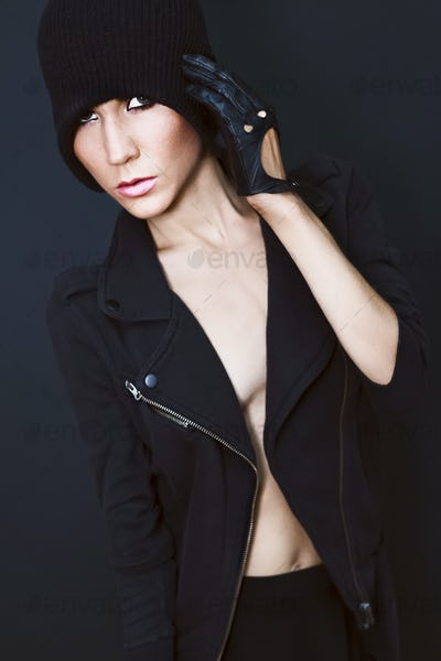 sexy model on black background in trendy gloves and jacket autum
