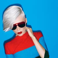 fashion blond lady with trendy hairstyle and sunglasses on a blu