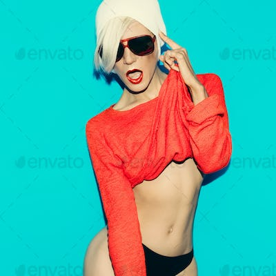 Sexy slim blonde on blue background in red sweater and fashionab