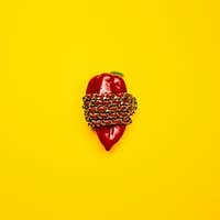 Conceptual fashion photography. Bright red pepper wrapped gold chain on a yellow background.