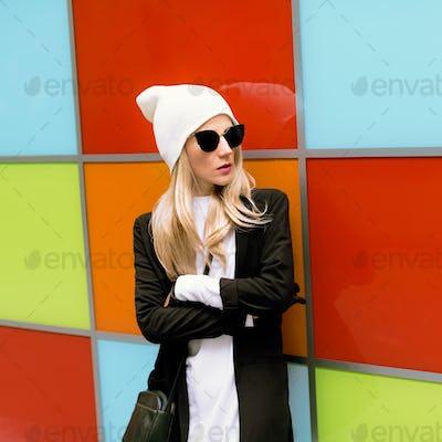 Fashionable blonde standing against a bright wall. Urban autumn