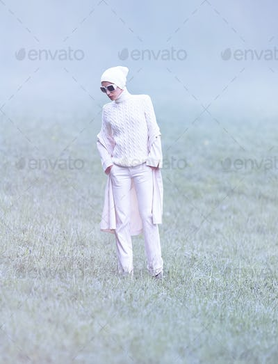 Cold fashion lady in a glamorous white dress in the autumn forest