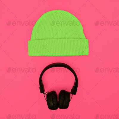 Stylish fashion accessories: hat and headphones on a pink backgr
