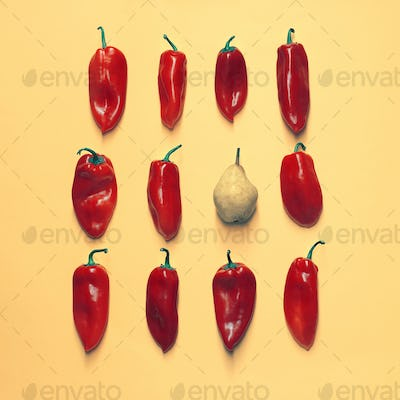 Set of neatly arranged bright peppers and one pear on a yellow background