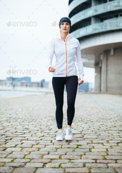 Woman power walking on urban street