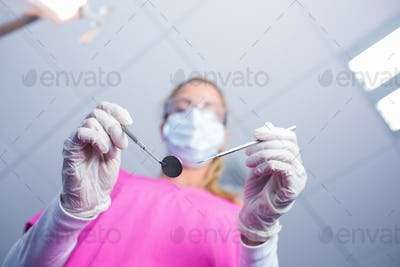 Dentist in surgical mask holding tools over patient at the dental clinic