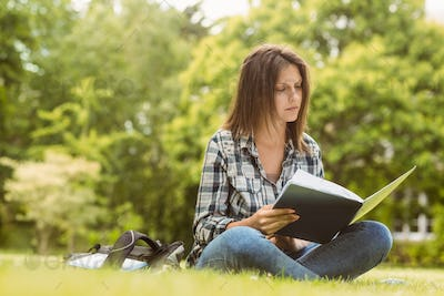 University student standing reading book in park at school