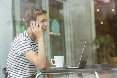 Smiling student using laptop and smartphone in cafe at the university
