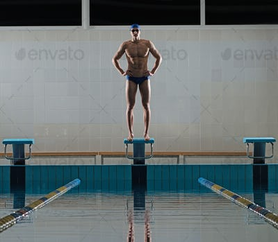 Young muscular swimmer standing on starting block in a swimming pool