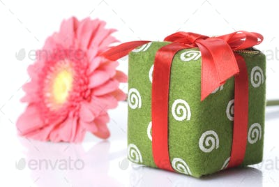 Gift with pink daisy-gerbera on white