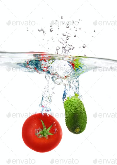 red tomato and green cucumber dropped into water isolated on whi