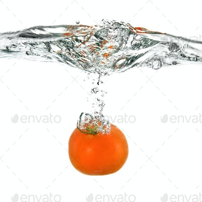 red tomato dropped into water isolated on white