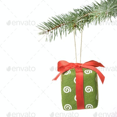 Christmas gift on fir tree branch with snow isolated on white
