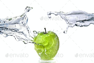 perfect fresh water splash on green apple isolated on white