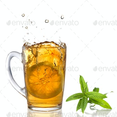 lemon dropped into tea cup with splash and mint isolated on whit