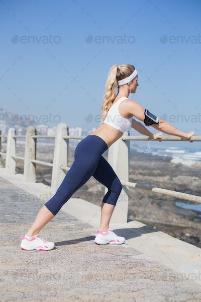 Fit blonde listening to music warming up on a sunny day