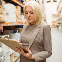 Focused female manager holding clipboard in a large warehouse
