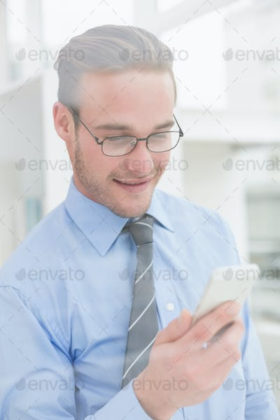 Cheerful businessman text messaging in his office