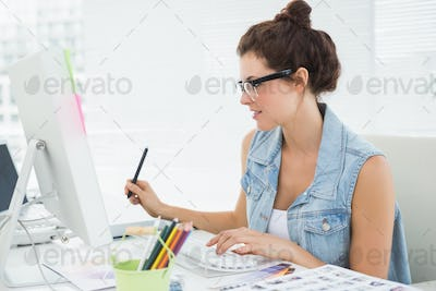 Cheerful casual businesswoman using computer and digitizer in the office