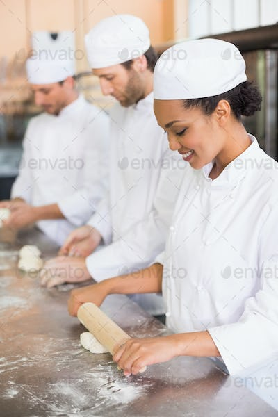Team of bakers working at counter in the kitchen of the bakery