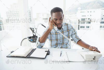 Serious businessman reading desk diary and phoning in the office
