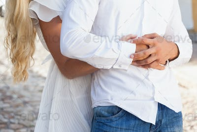 Cute couple hugging each other on a sunny day in the city