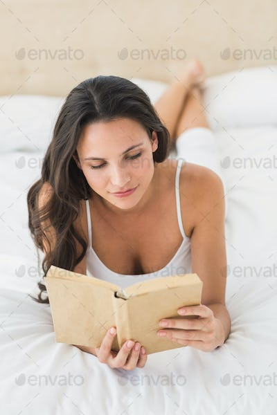 Happy brunette reading a book at home in bedroom