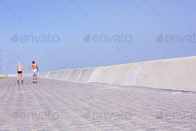 Fit couple rollerblading on the promenade on a sunny day