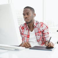 Focused businessman listening music and using digitizer in the office