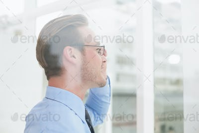Businessman standing with glasses smiling in his office