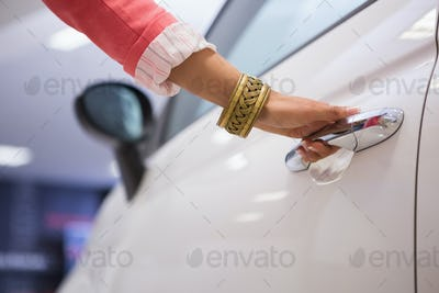 Woman holding a car door handles at new car showroom