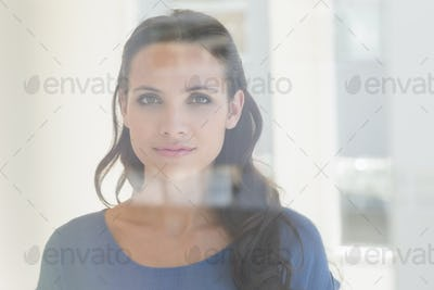 Pretty brunette smiling at camera at home beside window