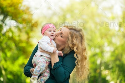 Mom kissing her daughter baby