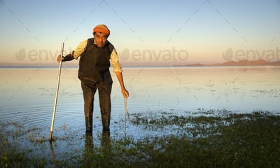 Mongolian Man Cleaning The Lake With The Cleaning Tool
