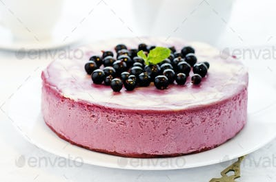 Black currant cheesecake on a white plate