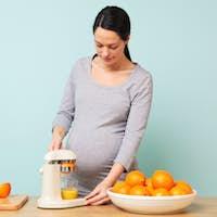 Pregnant woman making fresh orange juice.