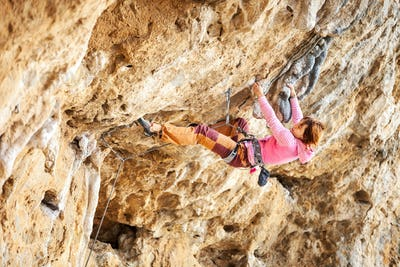 Young female rock climber on a cliff face