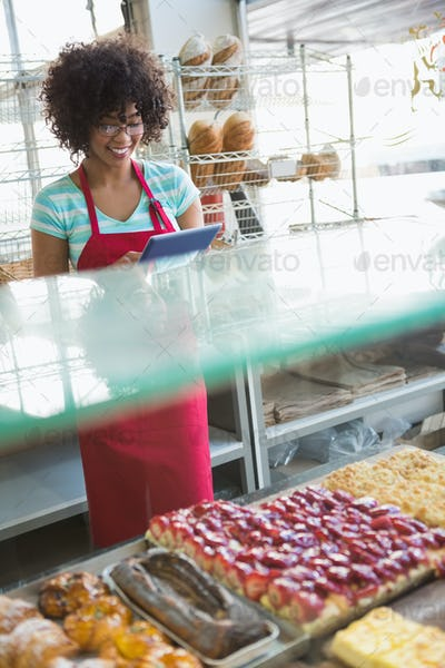 Smiling waitress using tablet pc at the bakery