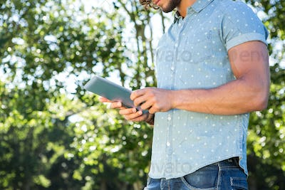 Young man using tablet in the park on a summers day