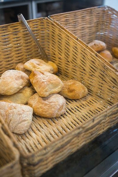 Baskets with delicious breads and tongs at the bakery