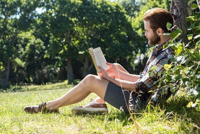 Handsome hipster reading book in park on a summers day
