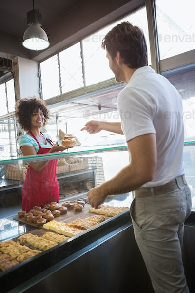 Pretty waitress giving food to customer at the bakery