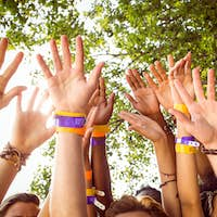 Happy hipsters with hands up at a music festival