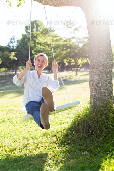 Happy blonde swing on a sunny day